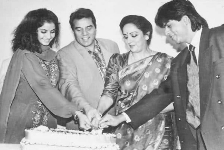 Divya Bharti, Dharmendra, Hema Malini and Shah Rukh Khan cutting a cake. Bharti and Khan starred in Dil Aashna Hai, which was produced by Malini | Photo from the book