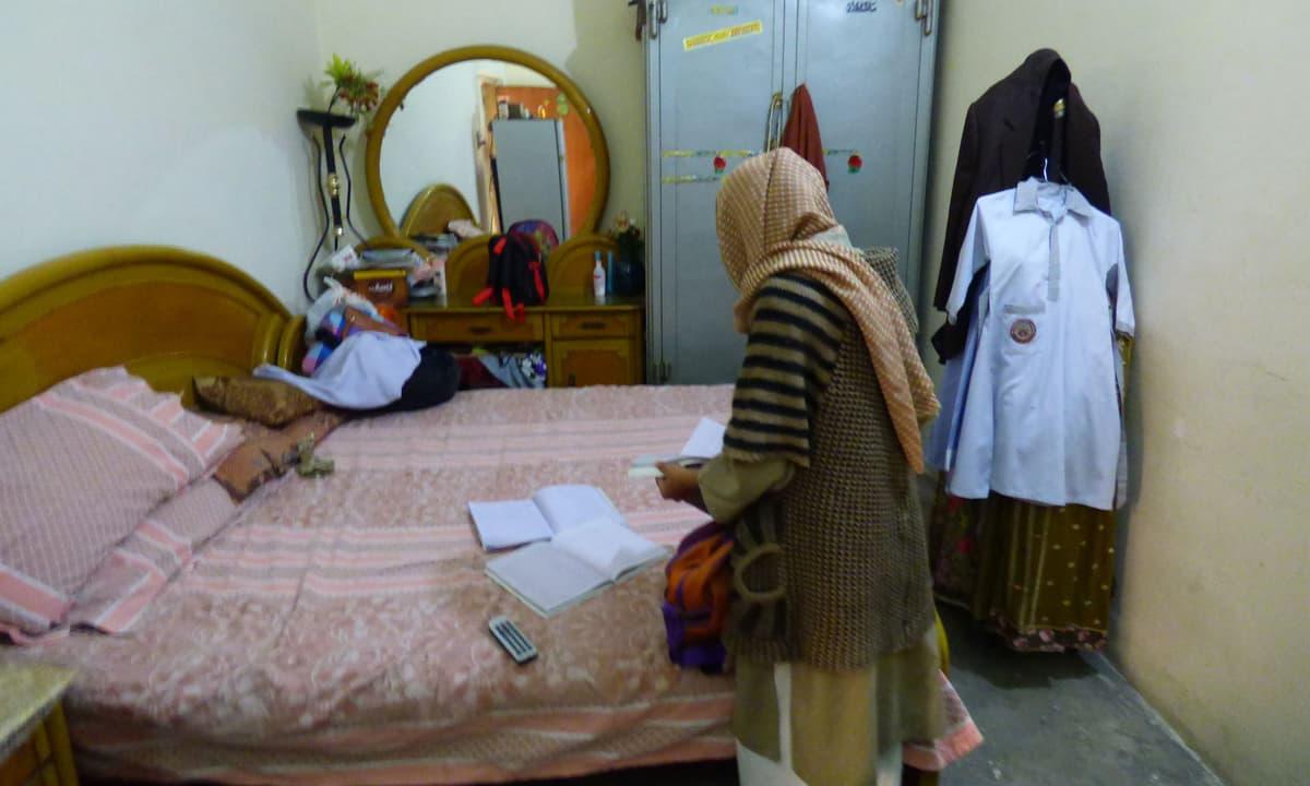 Zainab's mother, Nusrat Bibi, looks through her daughter's books in their home | Tariq Mahmood, White Star