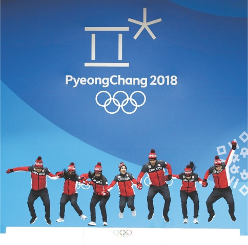 PYEONGCHANG: The Canadaian figure skating team jump in celebration after winning gold in the event on Monday.—AP