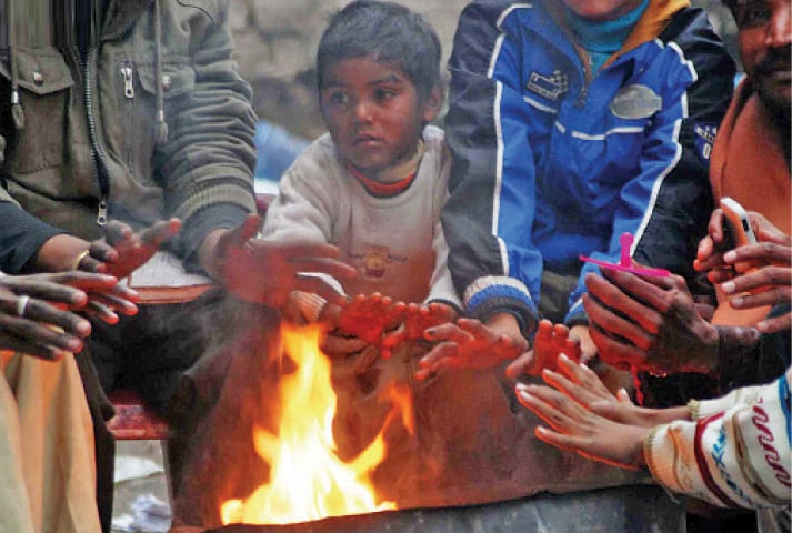A child huddles around a fire to keep warm. — Photo by Mohammad Asim