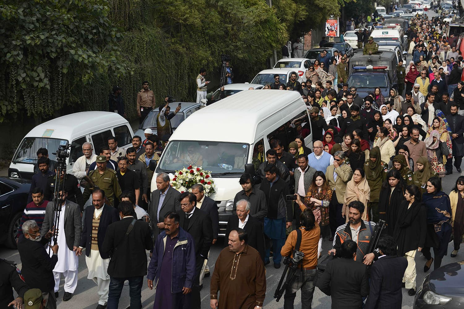 Mourners march alongside a vehicle carrying the coffin of lawyer and rights advocate Asma Jahangir during her funeral in Lahore. — AFP