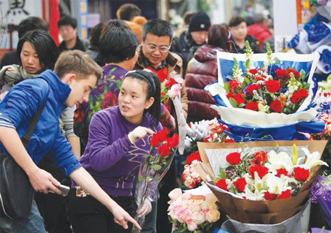 A FOREIGNER asks about the price of roses at Laitai flower market in Beijing on Feb 13, 2014 ahead of Valentine's Day.—China Daily