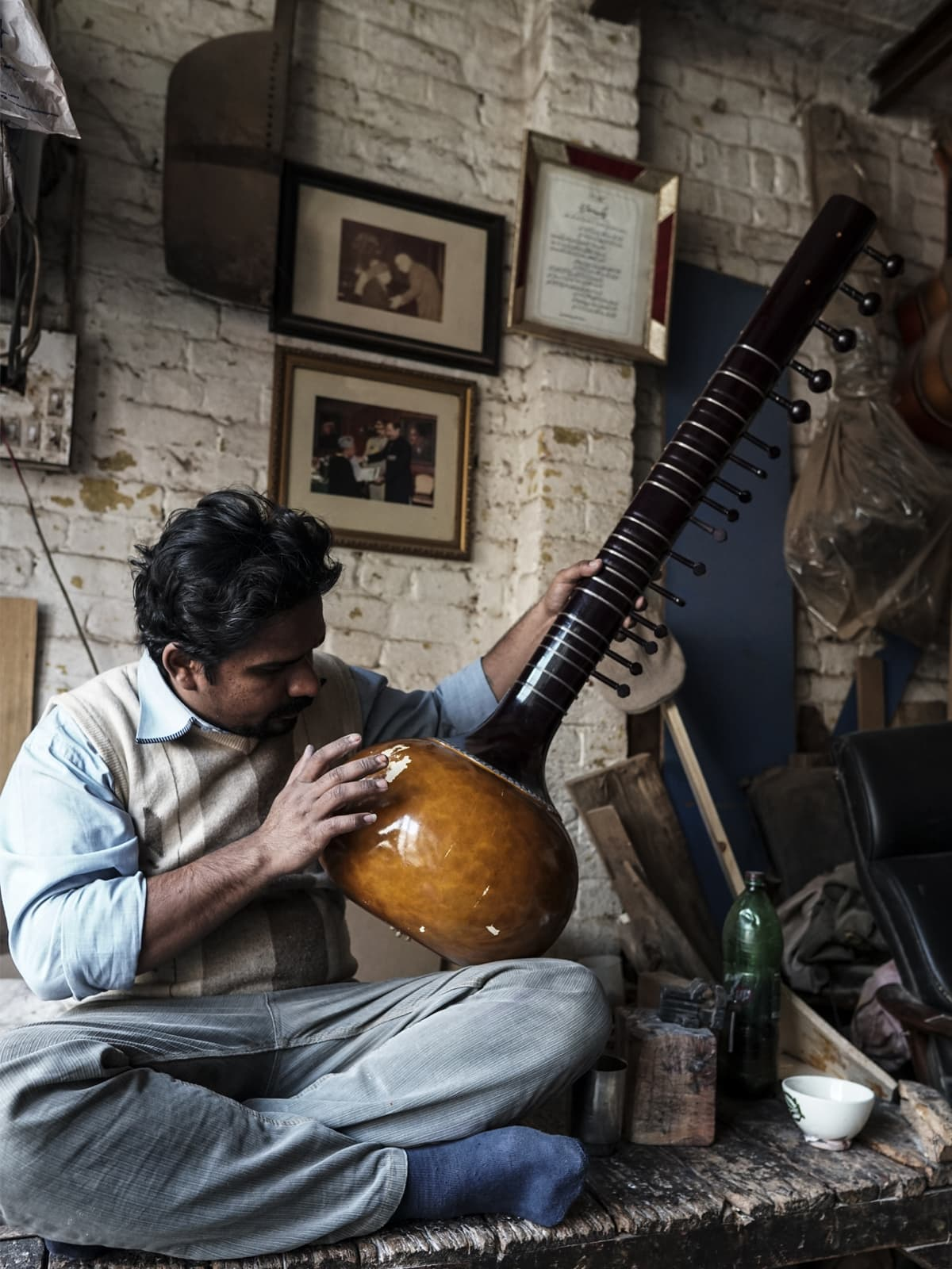 Ziauddin's son repairs the base of a sitar
