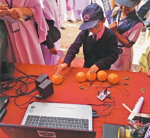 A young student is all smiles as he interacts with a science model at a stall.—Dawn