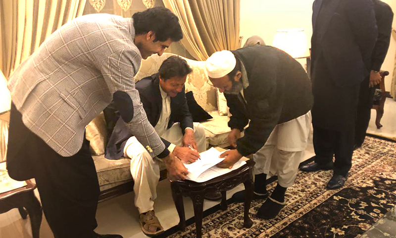 Imran Khan signing papers in Lahore at his nikah ceremony. ─ DawnNews