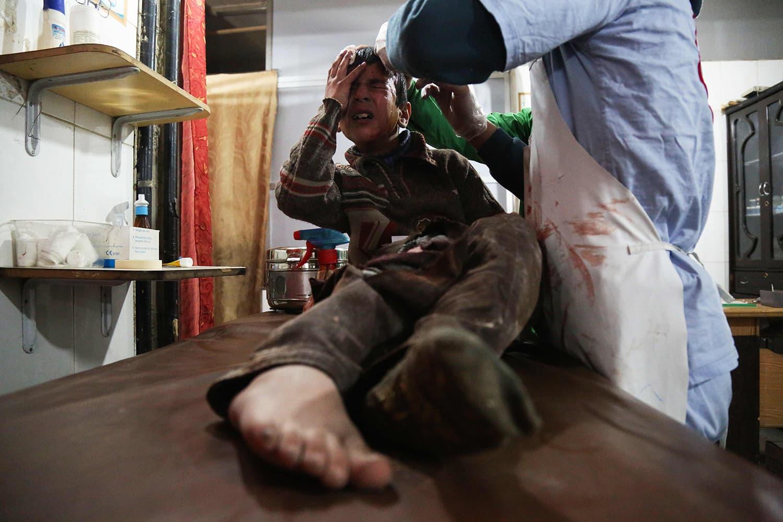 غوطہ میں بمباری سے زخمی 12 سالہ بچے کو ایک عارضی طور پر بنے ہسپتال میں طبی امداد دی جا رہی ہے— اے ایف پی