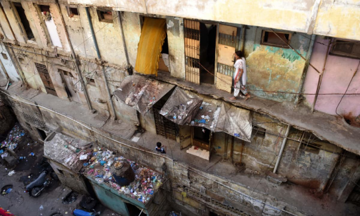 Rubbish overflows in front of a dilapidated building in Narayanpura, Karachi | Tahir Jamal, White Star