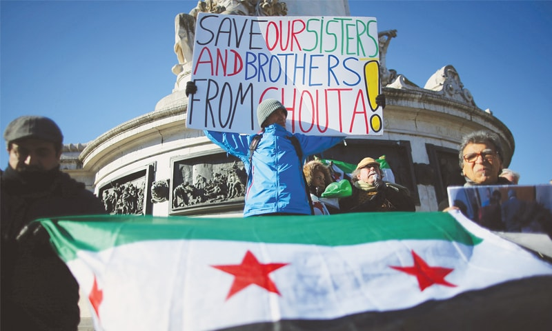 PARIS: Protesters hold a placard during a demonstration on Sunday to express solidarity with the people of Syria.—Reuters