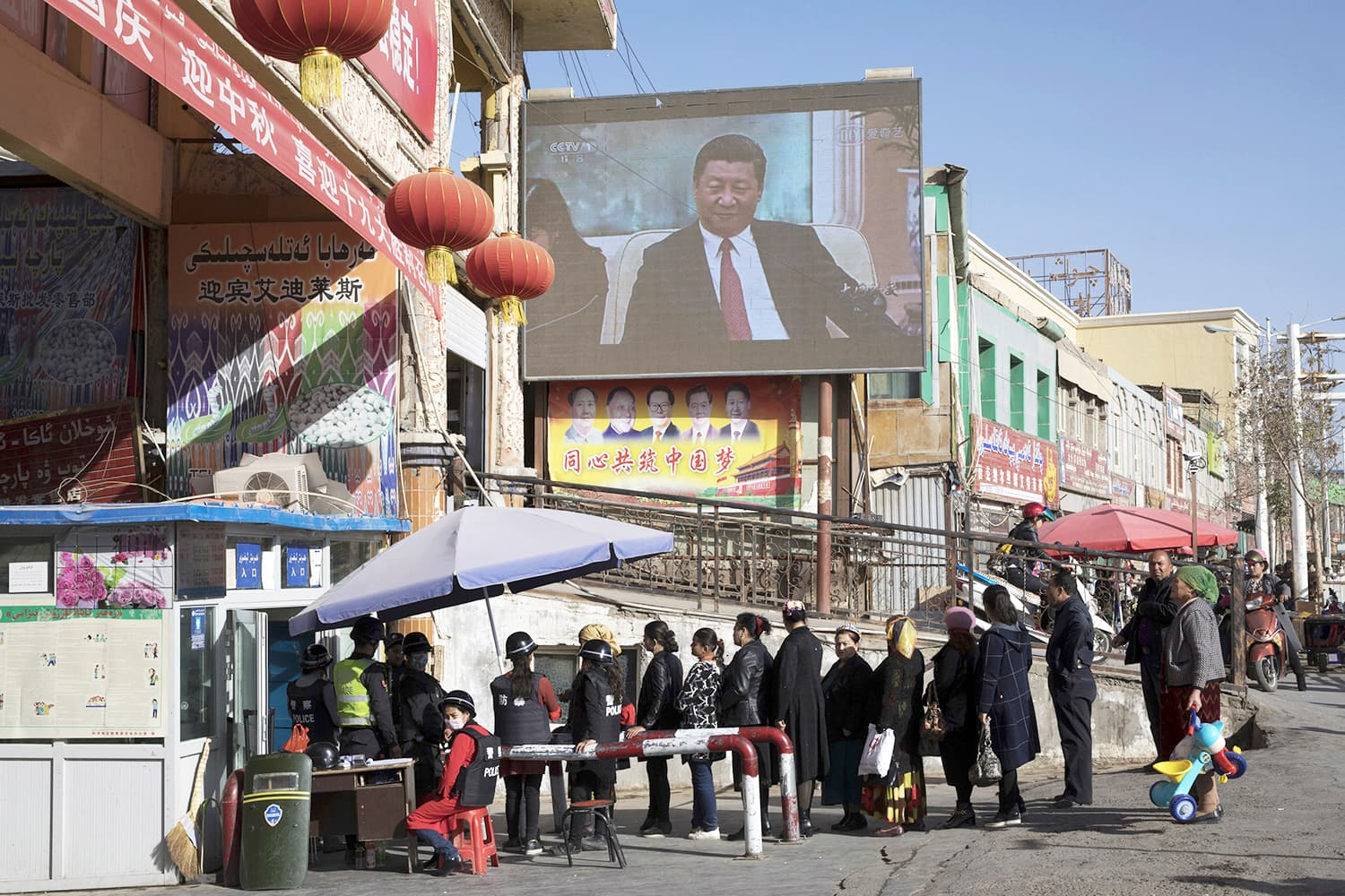 FILE - In this Nov. 3, 2017, file photo, residents walk through a security checkpoint into the Hotan Bazaar where a screen shows Chinese President Xi Jinping in Hotan in western China's Xinjiang region.  —AP