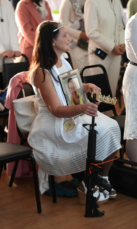 A worshipper holds her AR-15 semi-automatic rifle similar to the type which a teenager used to slaughter 17 students and school staff in Florida. ─ AFP