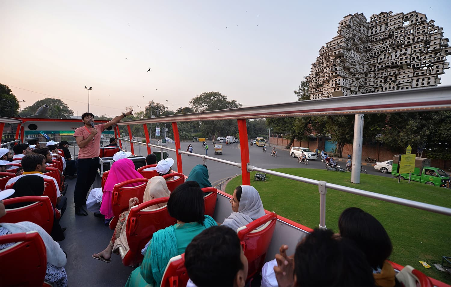 In this photograph taken on October 7, 2017, guide Farhan Bell (L) talks to tourists on a colourful double decker bus during a ride in Lahore. ─ AFP