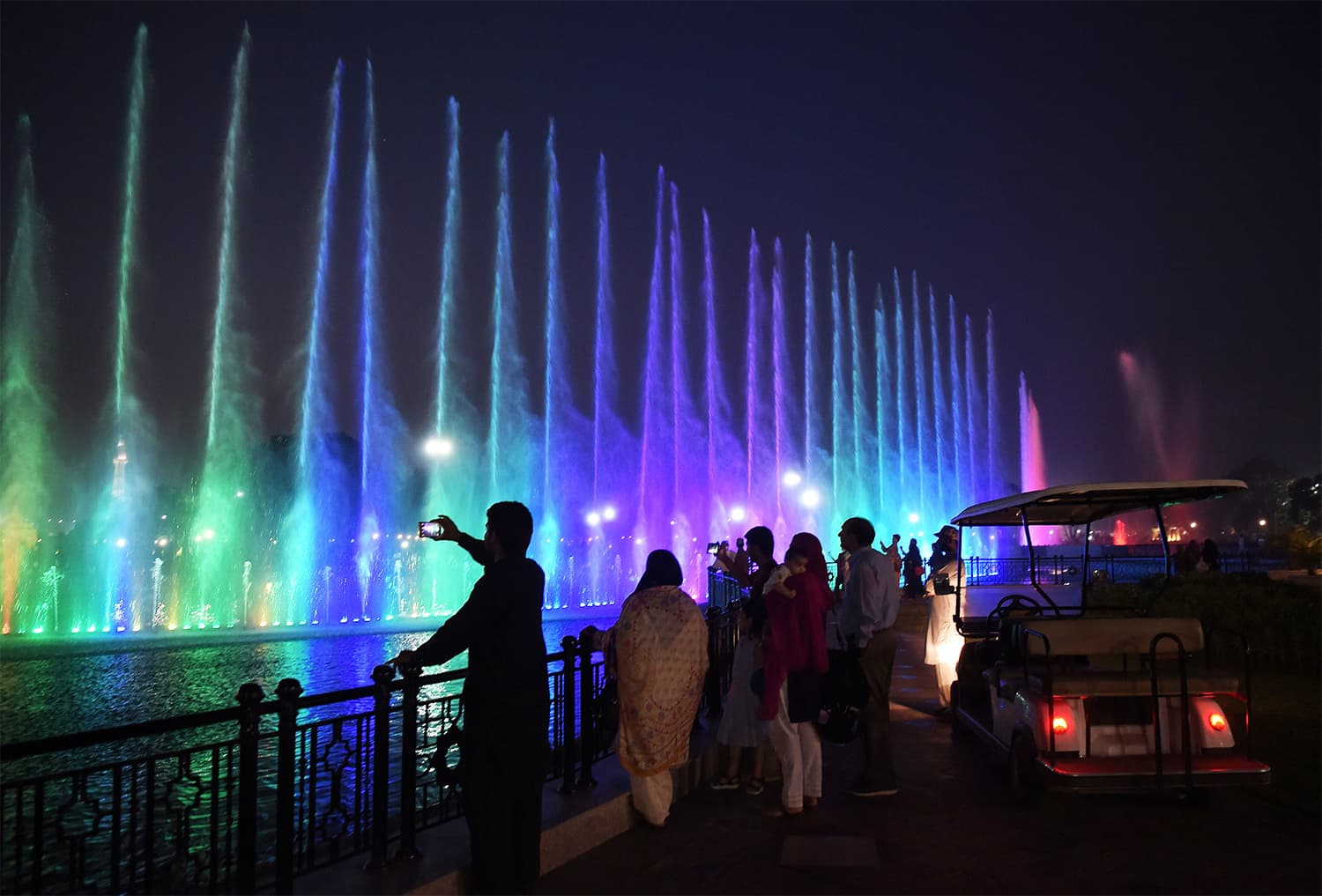 Tourists watch a colourful dancing fountain at Lahore's greater Iqbal Park. ─ AFP