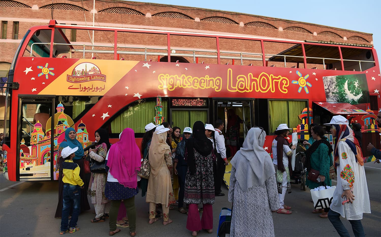 In this photograph taken on October 7, 2017, tourists prepare to board a colourful double decker bus before they start their tour of Lahore. ─ AFP