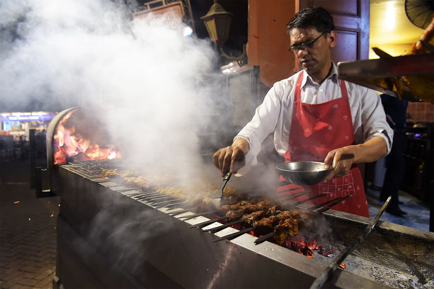 "A chef prepares bbq for tourists at Lahore's colourful ""food street"". ─ AFP"
