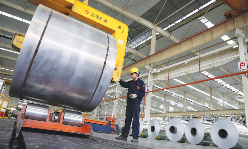 """This file picture taken on May 20, 2017 shows a Chinese worker checking aluminium tapes at an aluminium production plant in Huaibei, east China's Anhui province. China called on the United States on Friday to """"exercise restraint in using trade protection tools"""" after President Donald Trump announced plans to impose new tariffs on steel and aluminium.—AFP"""
