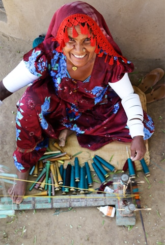 Fifty-year-old Tajju fills bobbins with different colours of thread