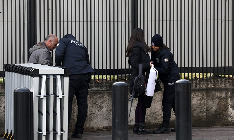 """Policemen search people outside the US embassy in Ankara, on March 5, 2018, as part of security measures set after the embassy was closed to the public over a """"security threat"""". — AFP"""