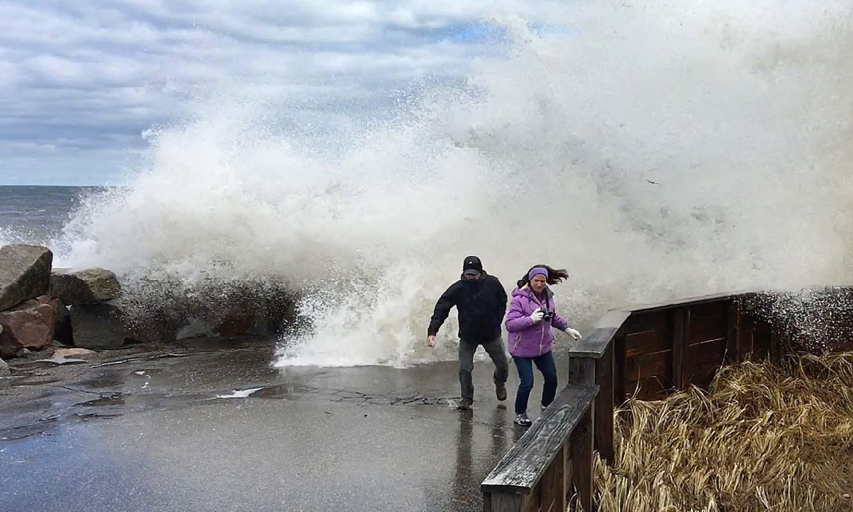 ساحل پر فوٹوگرافر تیز لہر کے ٹکرانے سے بچ کر بھاگنے کی کوشش کر رہے ہیں — فوٹو: اے پی