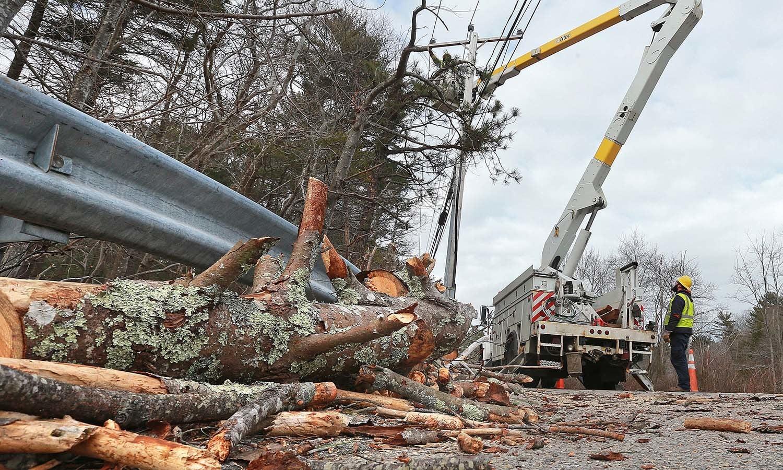 تباہ حال بجلی کی تاروں کی مرمت کی جارہی ہے — فوٹو: اے پی