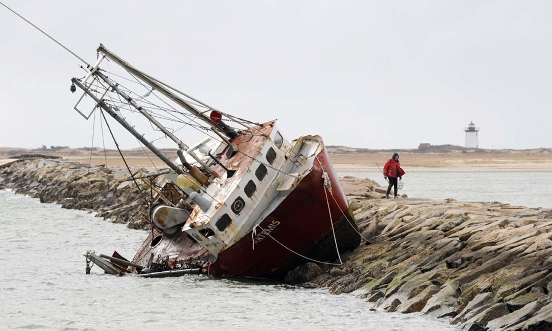 طغیانی نے کشتی کو ساحل پر لاپھینکا — فوٹو: اے پی