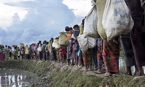 In this file photo taken on October 9, 2017 Rohingya refugees walk after crossing the Naf river from Myanmar into Bangladesh in Whaikhyang. — AFP
