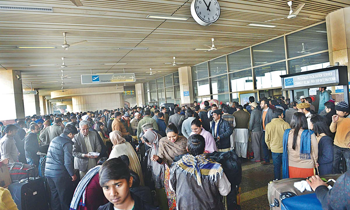 A crowd of passengers and their relatives at Lahore airport