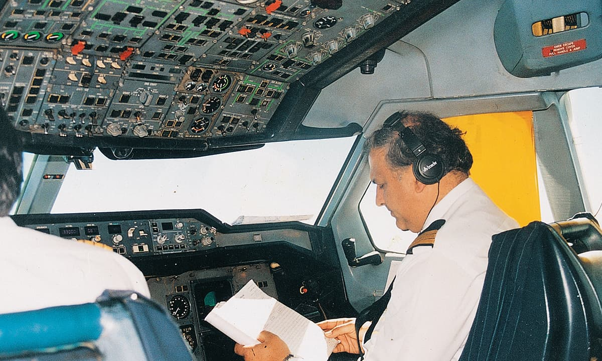 A pilot inside the cockpit of a PIA airplane;