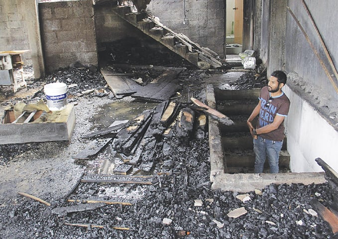KANDY: A man looks at a burnt home on Wednesday, a day after anti-Muslim riots erupted.—AFP