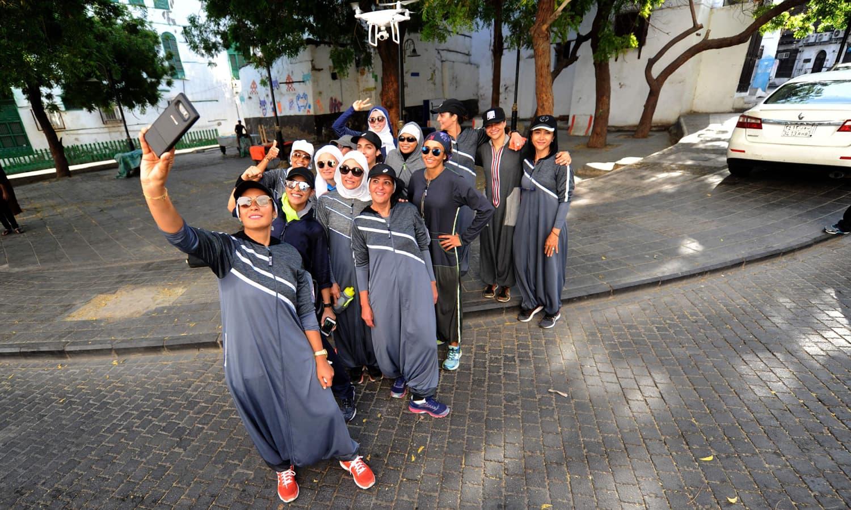دوڑ لگانے کے بعد خواتین سیلفی لینے کے اسٹائل میں تصویر کیلئے پوز دے رہی ہیں — فوٹو: اے ایف پی