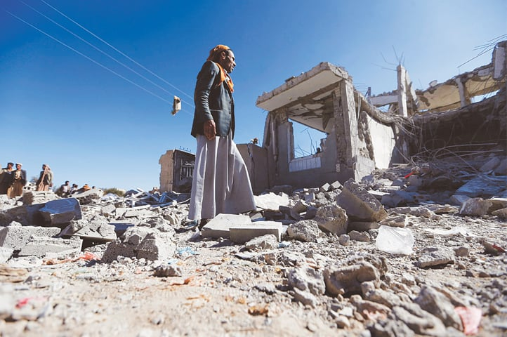 Sanaa: Yemenis look at the damage after an air strike by the Saudi-led coalition on Thursday.—AFP