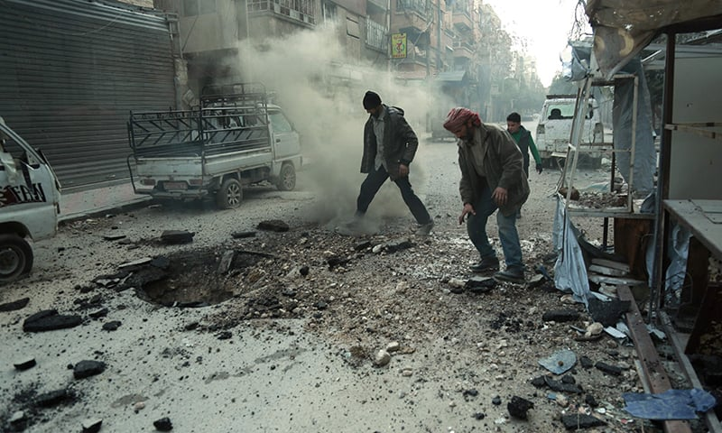 Syrian men check the damage following Syrian government shelling on the town of Douma in the rebel-held enclave of Eastern Ghouta. ─AFP