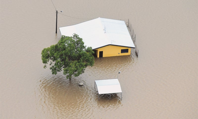 Ingham (Australia): A house is surrounded by floodwaters in the town of Ingham, Queensland, on Sunday.—Reuters