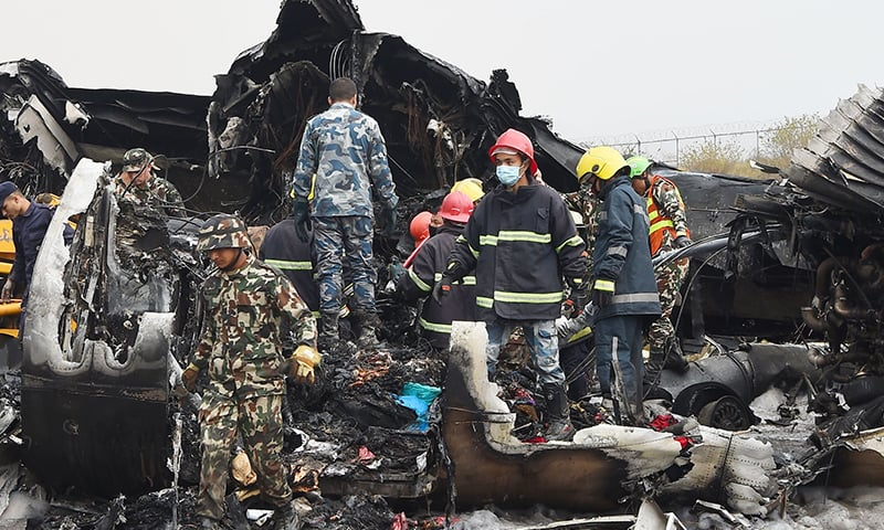Nepali rescue workers gather around the debris of an airplane that crashed near the international airport in Kathmandu. — AFP