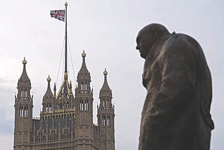 A STATUE of former British prime minister Winston Churchill stands near the Victoria Tower of the Houses of Parliament, as a British Union flag flies from a pole atop the tower, in London.—AFP