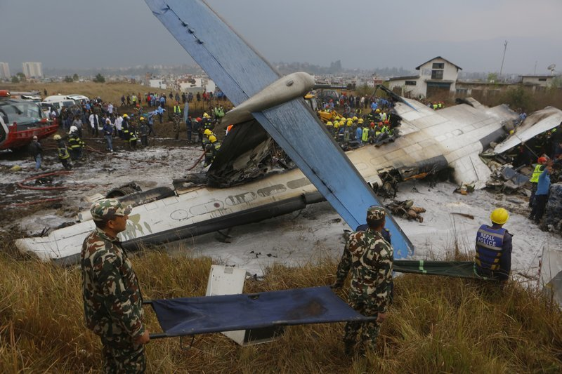 Nepalese rescuers work after a passenger plane from Bangladesh crashed at the airport in Kathmandu, Nepal, on Monday. — AP