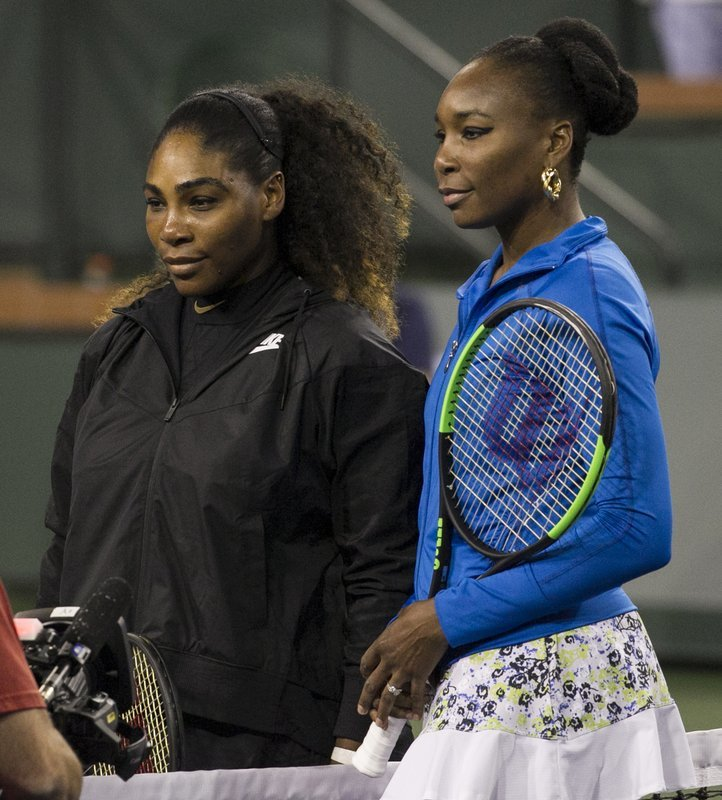 Sisters Serena Williams, left, and Venus Williams, right, meet on the court for a coin toss before their third-round match during the BNP Paribas Open tennis tournament on Monday. — AP