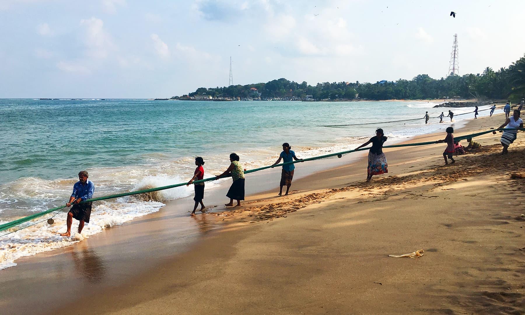 ساحل سمندر پر مچھلیاں پکڑتے ماہی گیر—تصویر امتیاز احمد