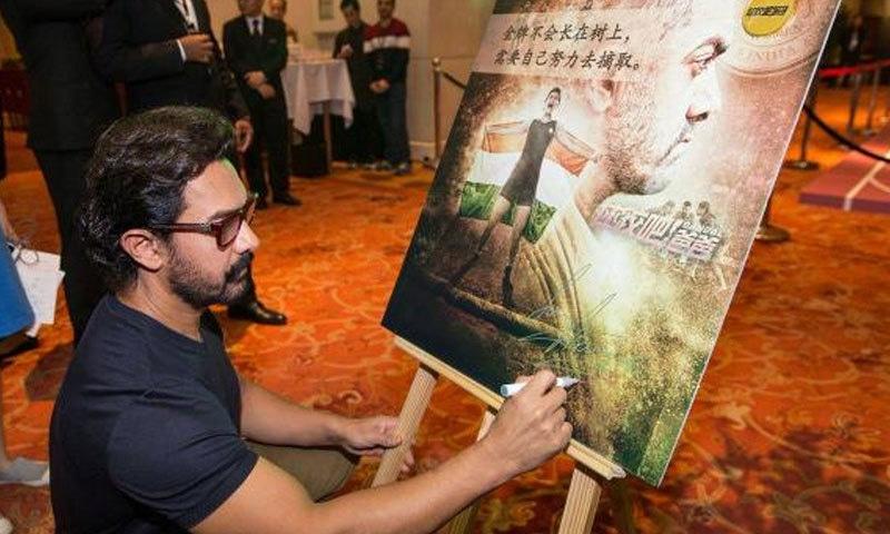 عامر خان چین میں دنگل کی تشہیر کے دوران فلم کی پینٹنگ بناتے ہوئے—فوٹو: پنک ولا
