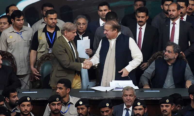 Punjab Chief Minister Shahbaz Sharif shakes hands with his brother and ousted prime minister Nawaz Sharif while Prime Minister Shahid Khaqan Abbasi (R) looks on, after being elected President of ruling PML-N at the General Workers Council in Islamabad on Tuesday. — AFP