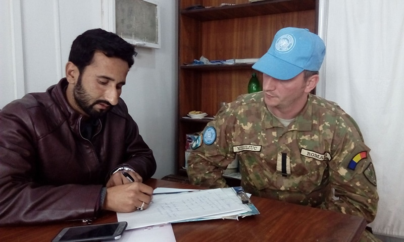 Police official Qazi Arslan (L) takes notes as he gets details of the incident at the LoC from a UN observer at Tehsil Headquarters Hospital Abbaspur. — Photo by Sardar Muhammad Zulfiqar in Abbaspur