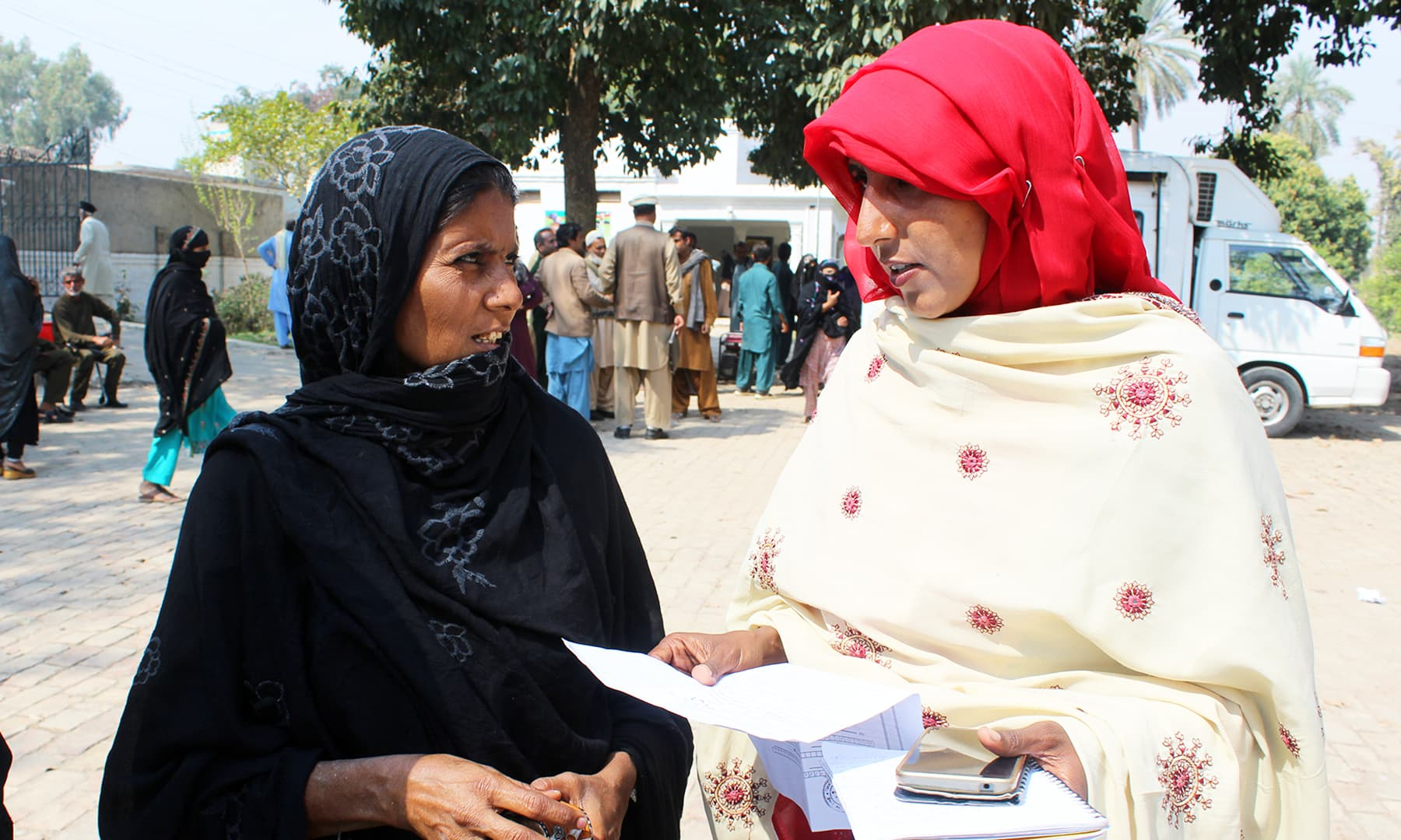 Social activist, Arshia, guides a woman about the process of obtaining a CNIC. — Photo by author