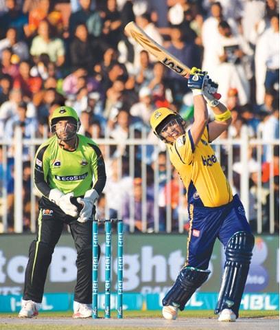 SHARJAH: Peshawar Zalmi's centurion Kamran Akmal plays a lofted shot as Lahore Qalandars' wicket-keeper Gulraiz Sadaf looks on during their Pakistan Super League match at the Sharjah Cricket Stadium  on Friday.—Courtesy PCB