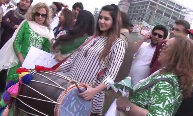 A girl beats the dhol outside the stadium. — DawnNews