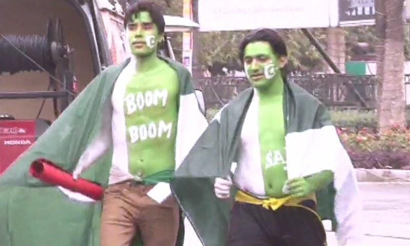 Two visitors painted in the colours of the Pakistani flag. — DawnNews