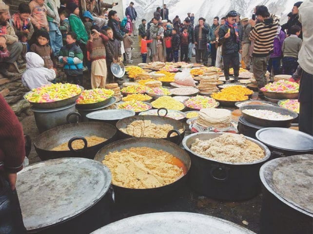 Local dishes are being prepared for distribution on Nauroz in Hisper, a village of Nagar district, on Tuesday.—Photo by writer
