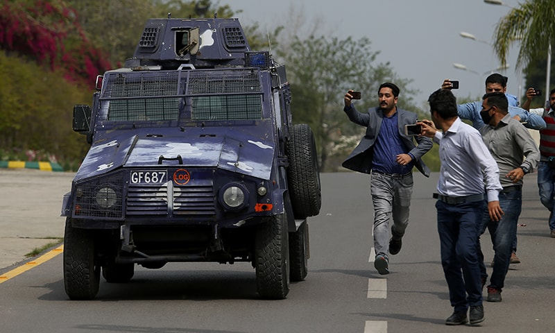 Journalists chase an armoured vehicle carrying Rao Anwar. — AP