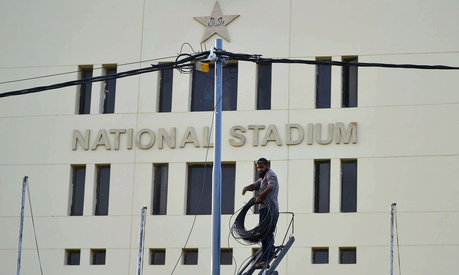 A worker installs cable outside the National Cricket Stadium ahead of the PSL final, on Tuesday. — AFP