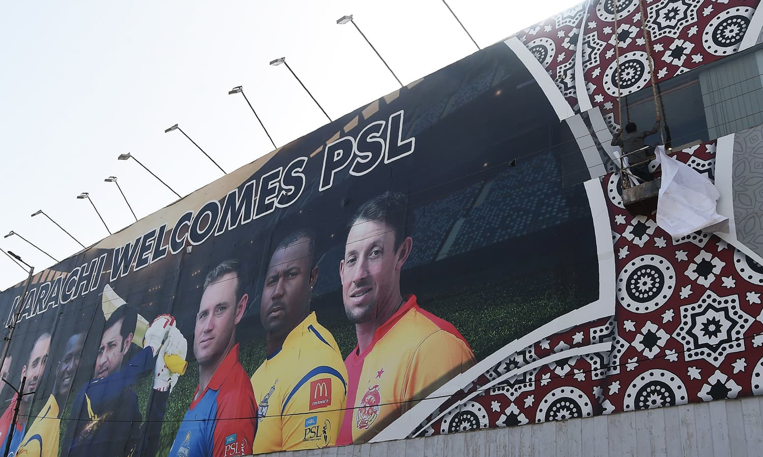 Workers fix a billboard featuring images of players ahead of the PSL final in Karachi on Tuesday. — AFP