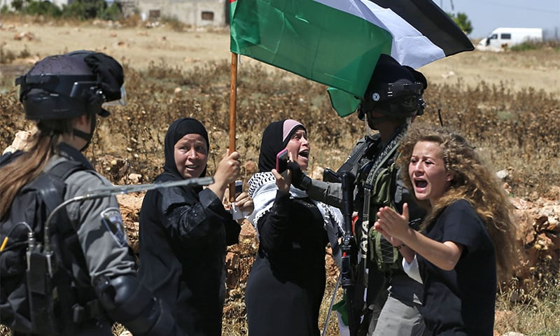 In this file photo taken on May 26, 2017 Palestinian Ahed Tamimi (R) reacts in front of Israeli forces during a demonstration on May 26, 2017, in the village of Nabi Saleh, north of Ramallah, in the Israeli-occupied West Bank. ─ AFP