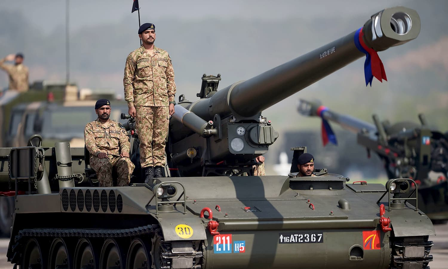 Pakistani military personnel travel on a tank during a Pakistan Day military parade in Islamabad. ─AFP
